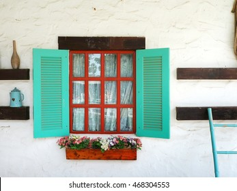 Window box on the white wall with colorful geranium