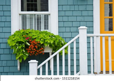 Window box planter and white stair railing and colorful house facade in Lunenburg, Nova Scotia