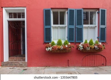 Window boxes and brightly colored facade of a home in downtown Charleston, South Carolina.
