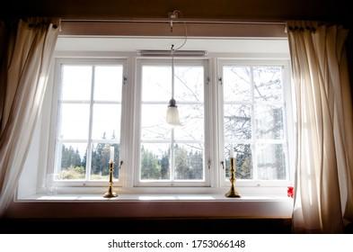 Ein Fenster mit hellen Vorhängen mit Blick auf den Wald