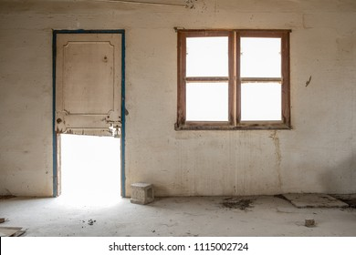 A window and broken door in the wall of a room in an abandoned, derelict building with stained walls.
