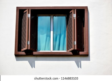 Window with brown bi fold wooden shutters on a white wall