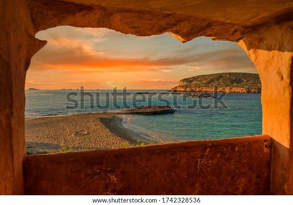 Window to Cala Comte de Ibiza at sunset, Spain