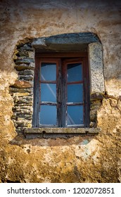 Window centered on a damaged wall of a ruined house
