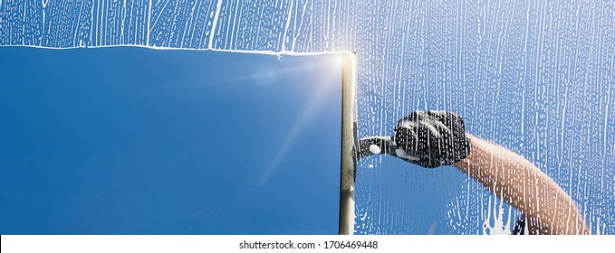 Window cleaner cleans window with foam and puller, banner size, banner size, panorama, with copyspace for your individual text. - Shutterstock ID 1706469448