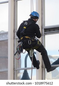 Window cleaner hangs from rope wearing safety harness and helmet
