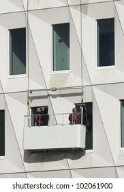 Window cleaners in hoist basket