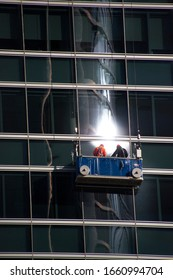 Window cleaners on its platform with different reflections, in Madrid, by Fermín Tamames