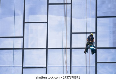 Window cleaners at work. Window cleaner, in the suspension system. Industrial mountaineering.