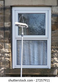 Window cleaning brush on pole spays water onto glass