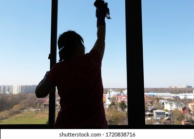 Window cleaning, silhouette of a woman washing the glass, inside view. Disinfection of home during the Covid-19 coronavirus pandemic