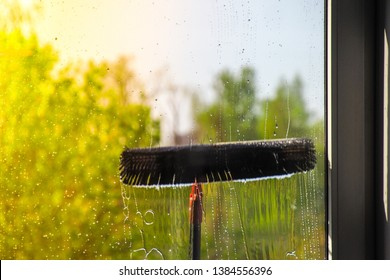 Window cleaning using telescopic water brush and wash system. Window cleaning from the outside with sky and trees in background