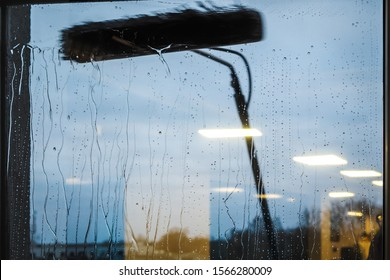 Window cleaning using telescopic water brush and wash system. Commercial window cleaning from the outside with sky in background