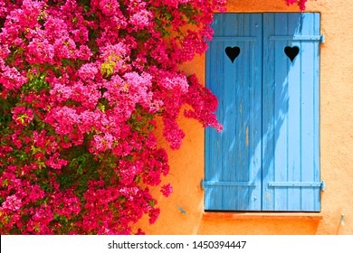 Window with closed blue shutters with heart-shaped cuts and bougainvillea flowers, French Riviera, South of France