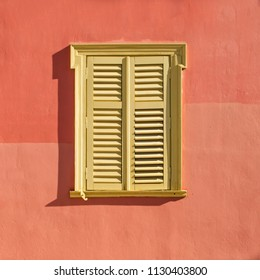 Window closed with bright yellow shutters isolated on background of bright terracotta wall. Cozy streets in the center of Athens. Plaka area. Greece. Summer greeting card, background.
