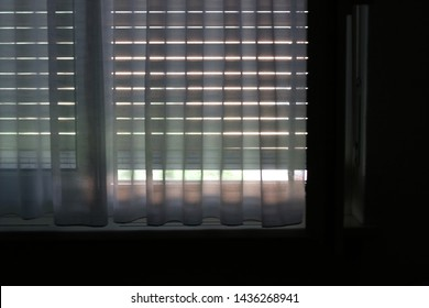 Window with closed curtains and shutter roll down. Interior of a room.