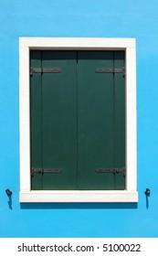 Window with closed green shutters, white outline, on a bright blue house in Burano Italy