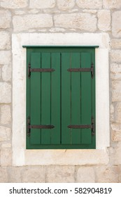 Window with closed green shutters in a white frame on the stone wall