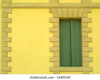 Window with closed shutters in rendered wall with stone edging