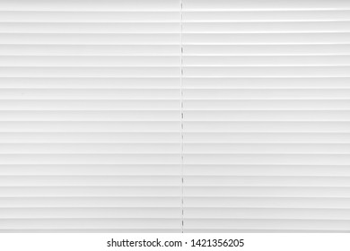 Window with closed white horizontal blinds as background