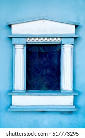 Window with columns and velvet curtains on the blue wall