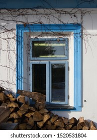 The window of a country cottage and stacked wood ready for heating in winter. White facade, blue window and brown color of the wood logs.