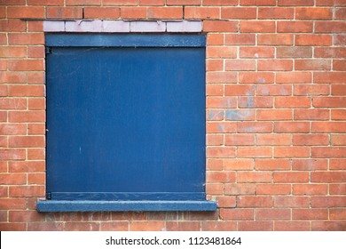 Window covered with blue board in brick wall, great copy space