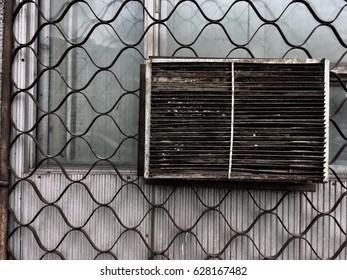 Window covered with metal grill and old dirty air conditioner.