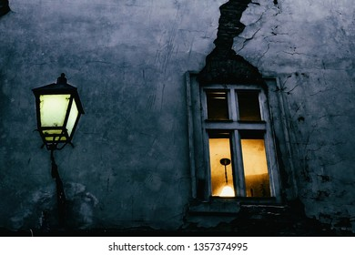 Window with a crack and street lamp in the evening in one of the small streets of Bratislava Old city center, Slovakia