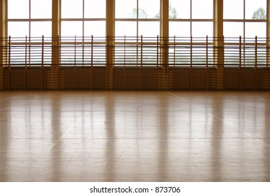 Window curtain wall reflecting at parquet floor at school gym.