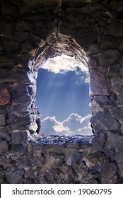 Window cut into a stony citadel with a view of puffy white clouds with the sun's rays burning through them.