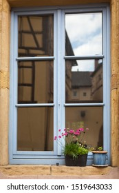 Window decorated with red little flowers in Colmar, France, Europe.  Window flowerpot with beautiful blooming flowers.