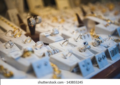 Window display at jewelry shop presenting necklace, rings and earring sets. Tilt-shift lens used to accent the specific objects and to emphasize the attention on it.