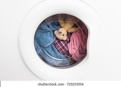 Window door of washing machine with laundry and toy teddy bear inside who takes a look out (copy space)/Wild Carousel Ride