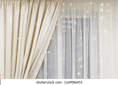 A window draped with a white curtain. Evening romantic and mysterious holiday Christmas curtains.