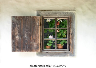 Window with flowers in a clay hut