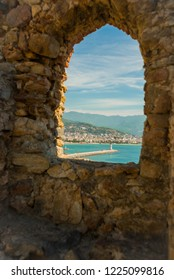 Window in the fortress in the stone wall. View of landscape and lghthouse of Alanya port , Alanya, Turkey