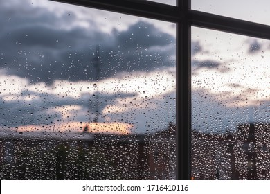 Window frame perspective with raindrops at sunset