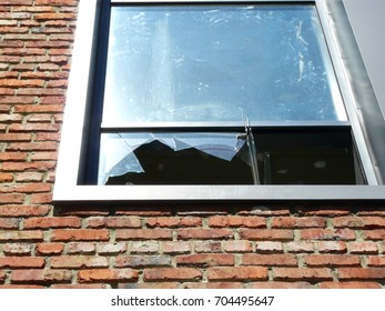 Window glass broken during war shooting. Bright blue sky reflected in the glass. Red brick wall. Shining in the sunlight metallic frame.