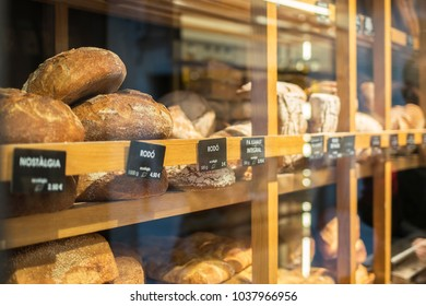 Window glass with exhibited bread loaves and buns for sale in city baker.