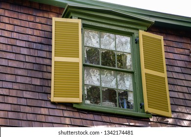 window with gold shutters white lace curtain with cat design