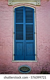 Window with green shutters on a red building located in the French Quarter of New Orleans LA.USA.  Many interesting doors and balconies are located in the Quarter.