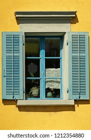 Window with green shutters on yellow house