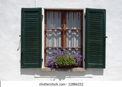 window with green shutters and purple flowers against a white wall