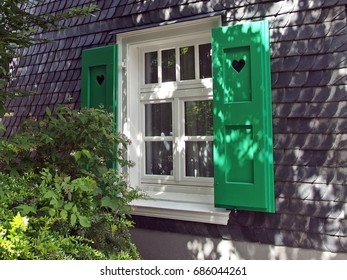 Window with green shutters in slate-covered wall