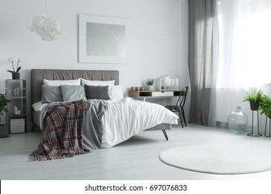 Window with grey and white curtains in spacious room with bed