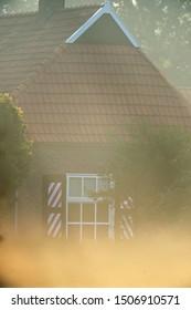 Window of historic dutch farmhouse on misty morning in summer.