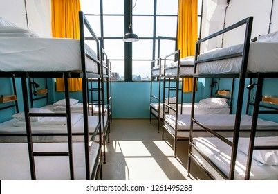 Window of a house with many bunk beds. Light bedroom with clean sheets.