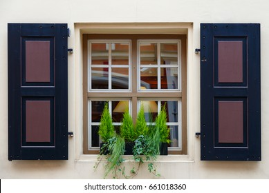Window of the house with open shutters and flowers on the windowsill