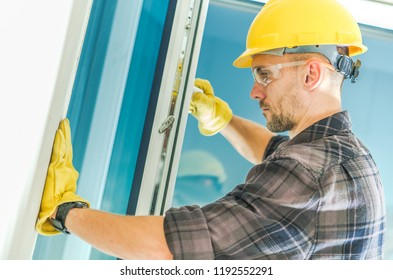 Window Installation by Caucasian Worker Wearing Yellow Hard Hat. Construction and Housing Industry.